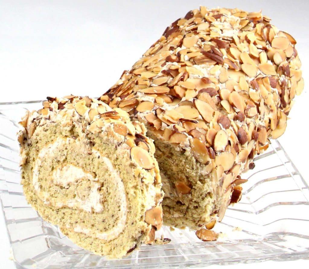 Ořechovo-kávová piškotová roláda na skleněném tácu, posypaná plátky ořechů
