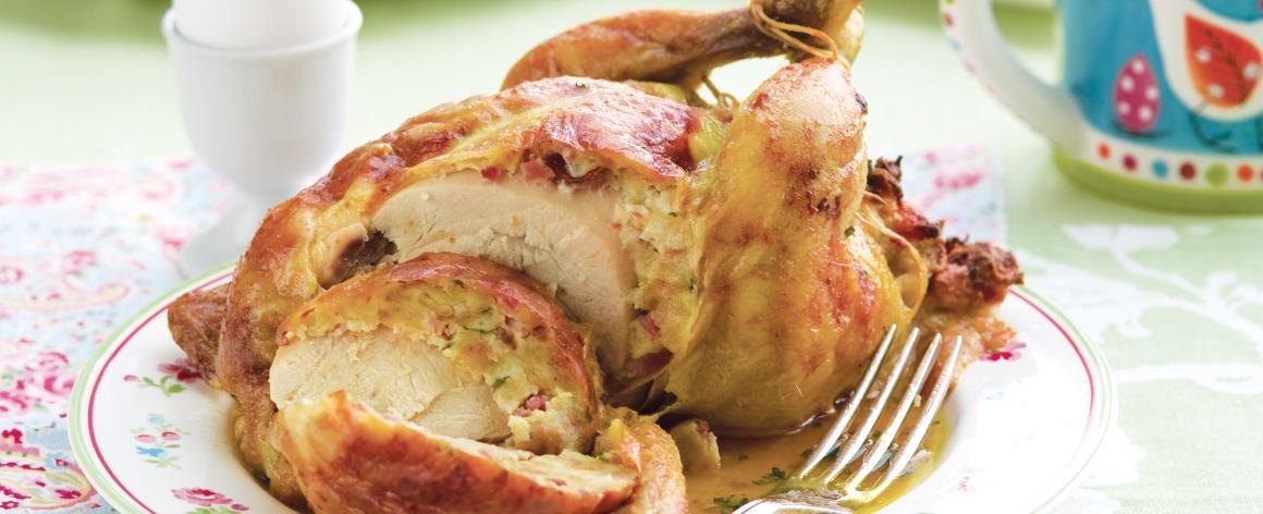 Rozkrojené celé pečené kuře s nádivkou na talíři.