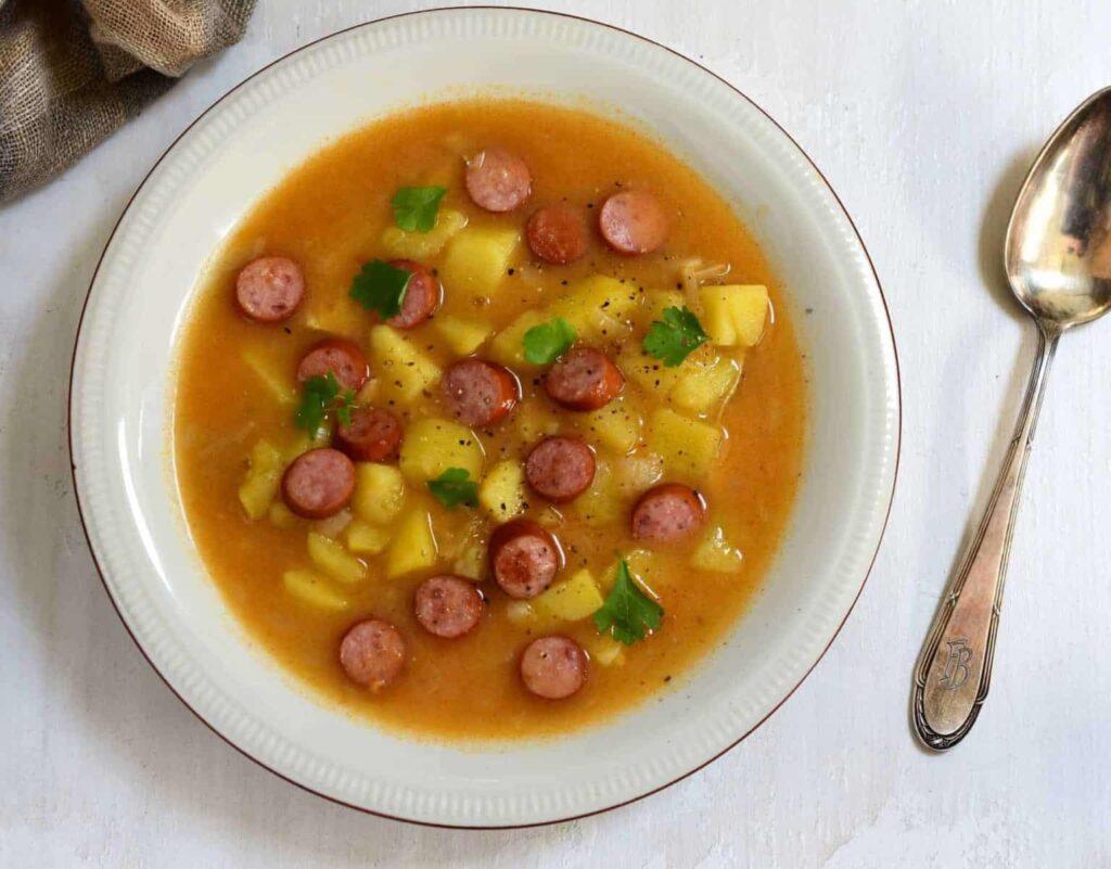 Talíř s polévkou s klobásou a bramborami.