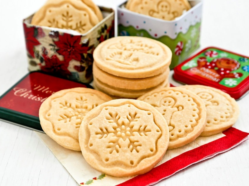 Lisované linecké cukroví s vánočními motivy, s plechovými krabičkami v pozadí