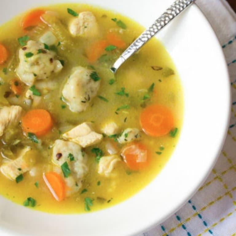 Rybí polévka z tresky na talíři s lžící