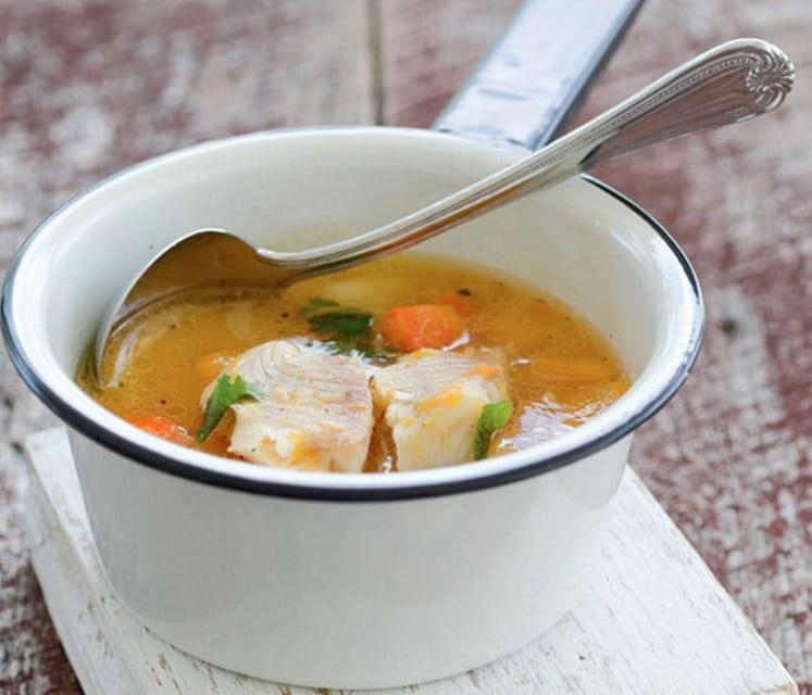 Hrnek s polévkou z filé s ponořenou lžící
