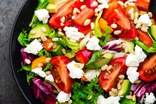 Zeleninový salát se semínky a sýrem na černém talíře