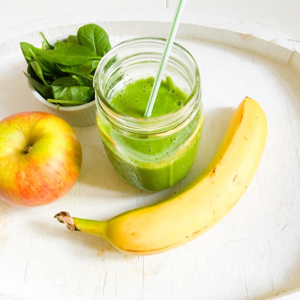 Sklenice špenátového smoothie s jablkem a banánem.