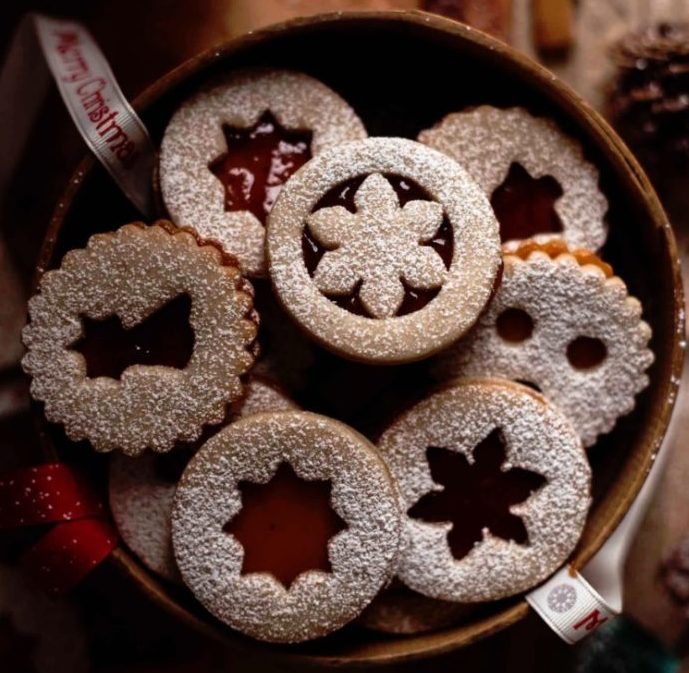 Linecké cukroví v misce posypané moučkovým cukrem s vánočními vykrojenými motivy