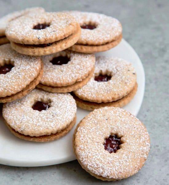 Kulaté linecké cukroví s hvězdičkou posypané moučkovým cukrem naservírované na talíři