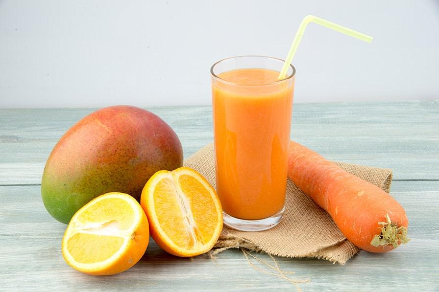 Pomerančové smoothie ve sklenici s mrkví a mangem.