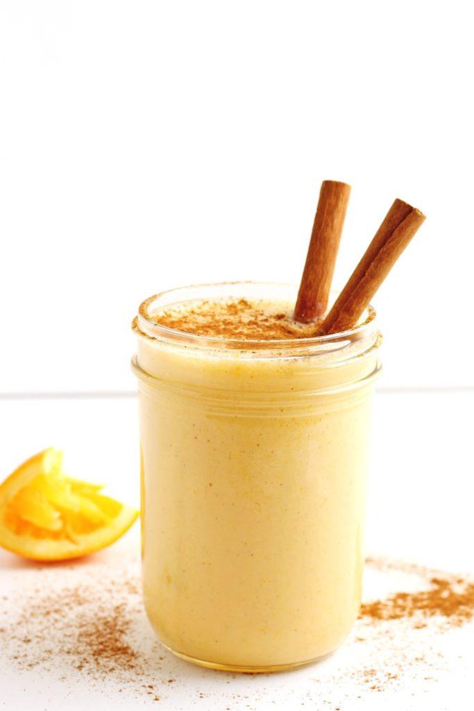 Pomerančové smoothie ve sklenici posypané skořicí.