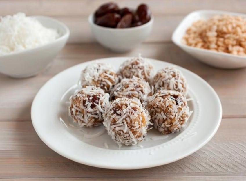 Datlové nepečené kuličky obalované kokosem na bílém talířku
