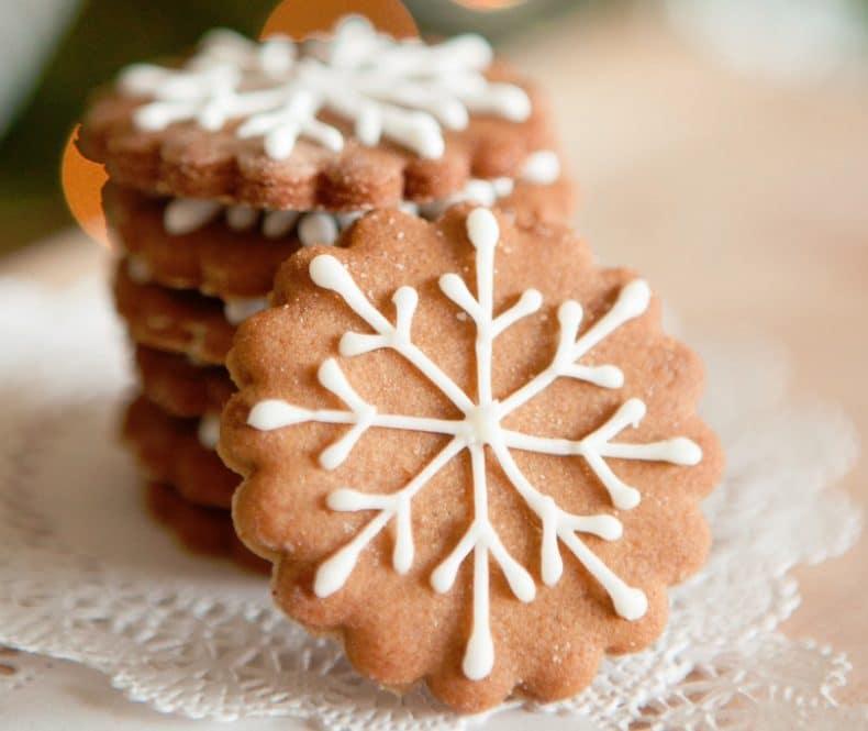 Vánoční perníkové vločky s bílým zdobením ze sněhu.