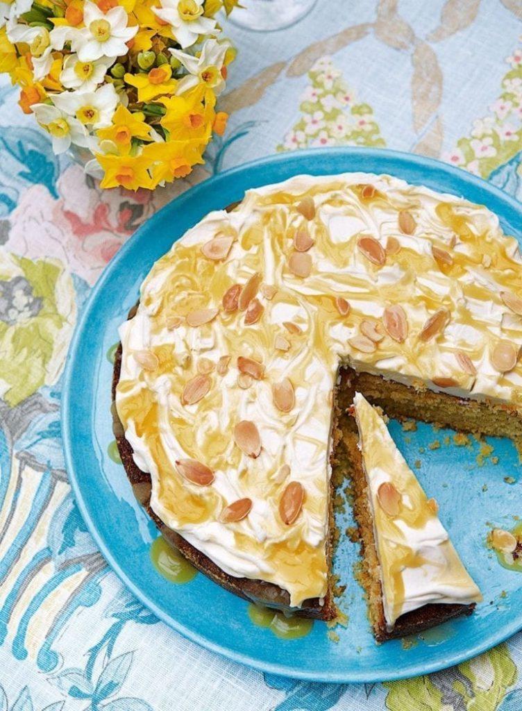 kulatý koláč s tvarohovou polevou a nasekanými mandlemi