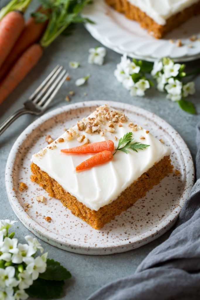 koláč z mrkve s cukrovou polevou, oříšky a baby mrkví jako dekorace