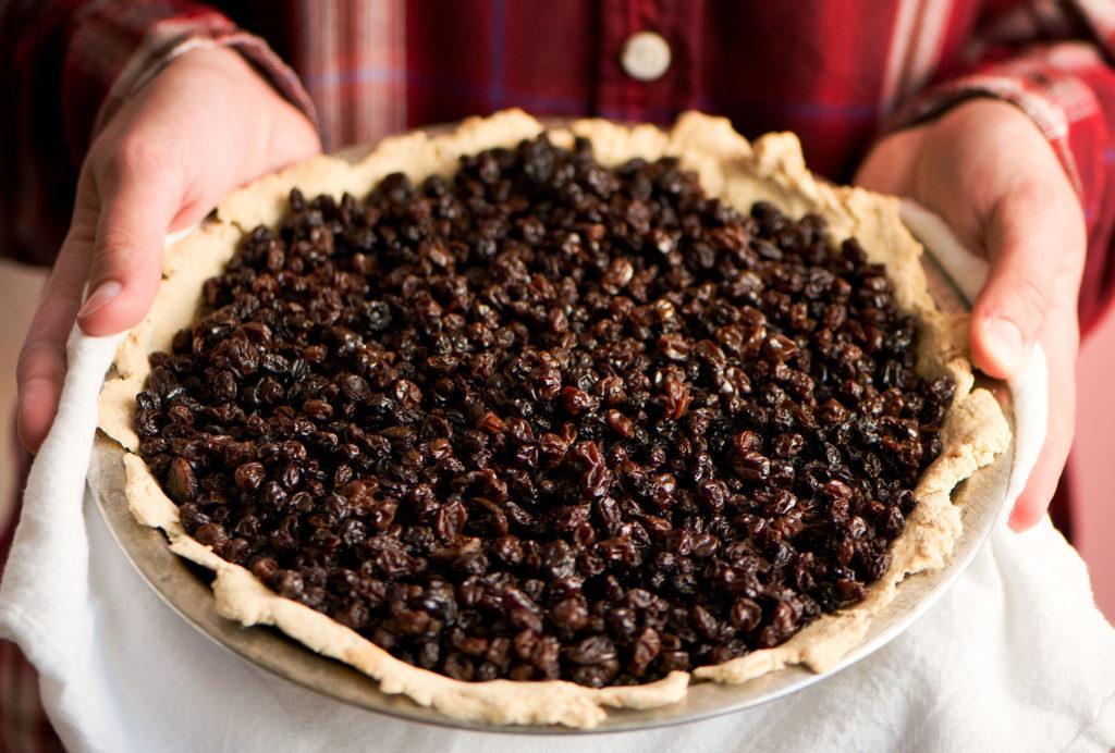 tvarohový kulatý koláč pokrytý černým rybízem