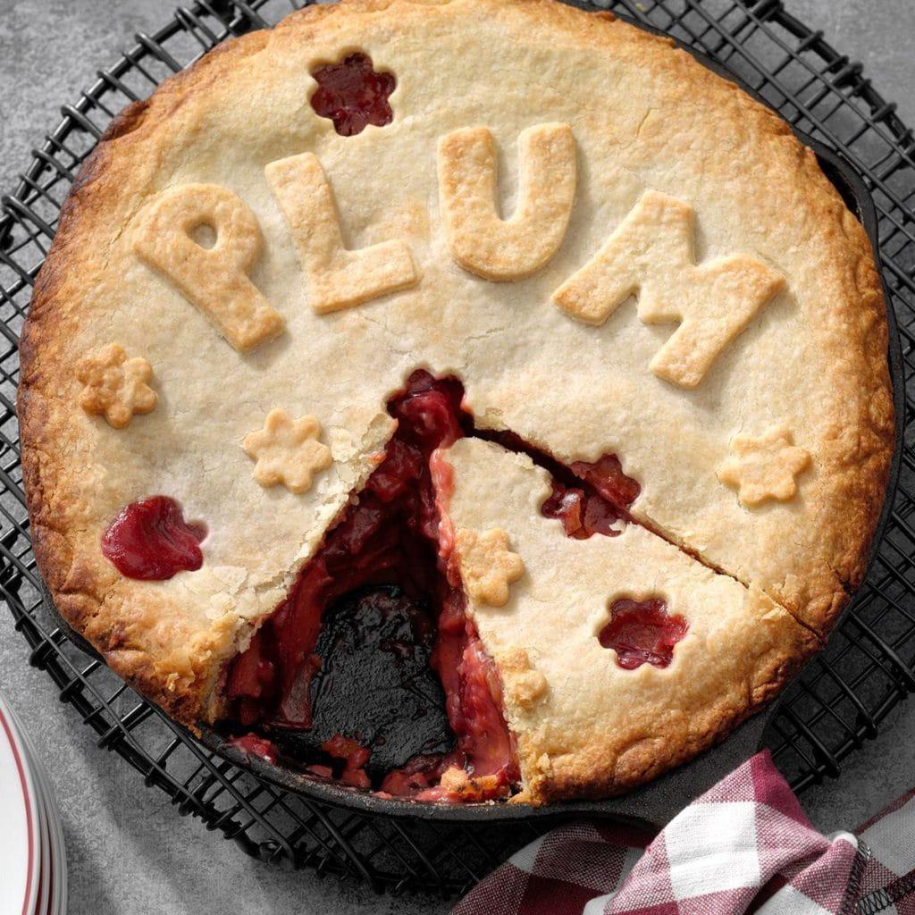 klasický koláč se švestkovou náplní a nápisem PLUM z těsta na povrchu