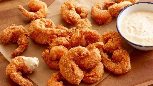 Smažené křupavé krevety v trojobalu si můžete dát třeba s hranolkami.