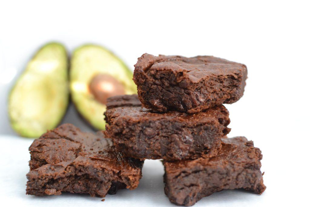 čtyři kousky brownies s avokádem v pozadí