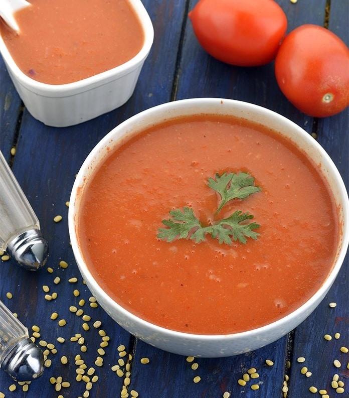 Rajská polévka v misce ozdobená petrželkou,, na modré podložce s rajčaty a kořením