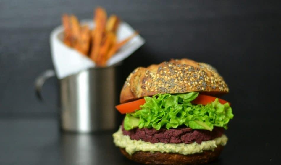 Burger s řepovým falafelem, hummusem, salátem a rajčetem; v pozadí plechový hrnek s hranolkami