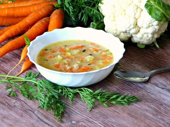 květáková polévka v bílé misce; v pozadí mrkev a květák