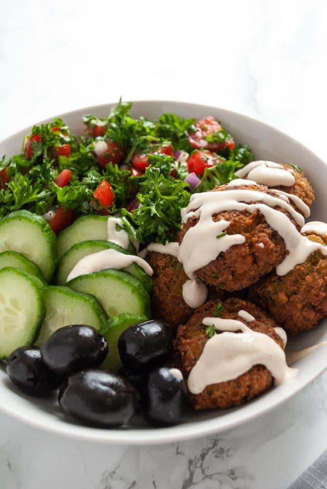salát s falafelem, olivami, okurkou a jogurtovou zálivkou v misce