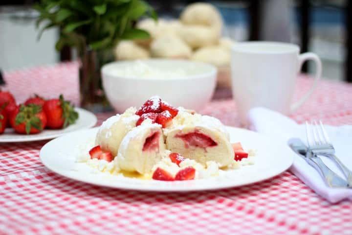 Ozdobené tvarohové knedlíky s jahodami na stole s růžovým ubrusem