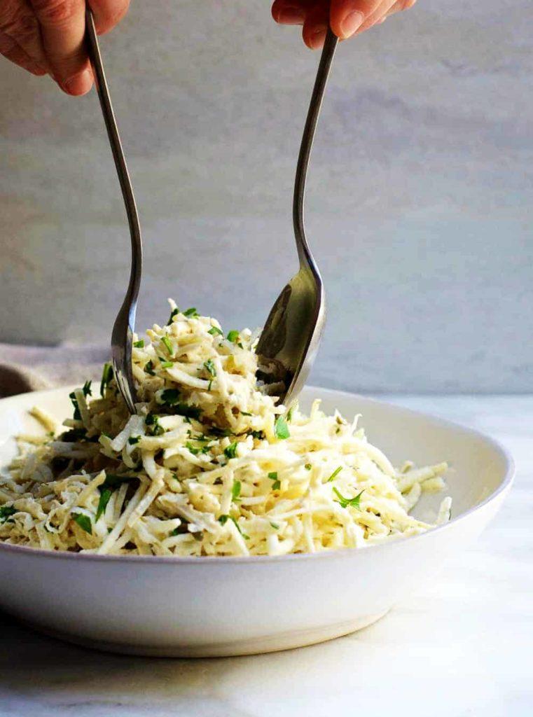 Celerový salát v bílé misce promíchávaný vidličkou a lžící