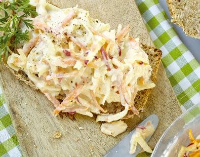 Plátek chleba namazaný celerovo mrkvovou pomazánkou na prkýnku