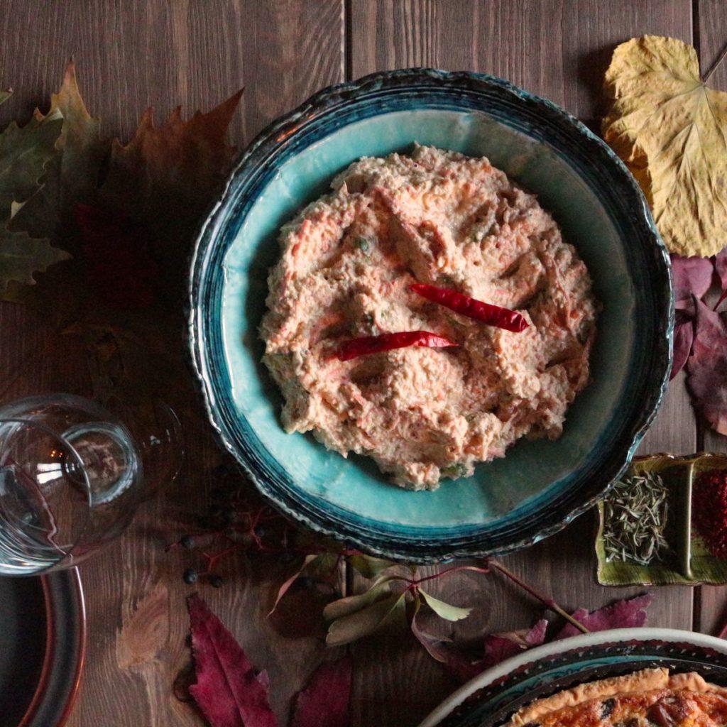 Pomazánka z pečeného celeru v modré misce na stole s vínovou skleničkou a podzimním zátiším
