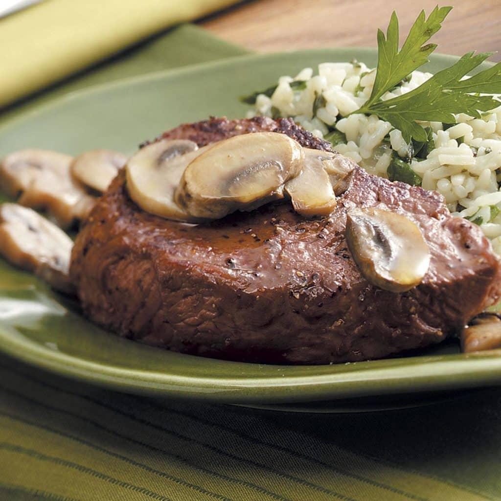 Plátek krkovice s houbami a salátem na talíři