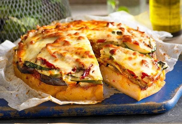 Rozkrojený koláč z polenty se zeleninou a sýrem