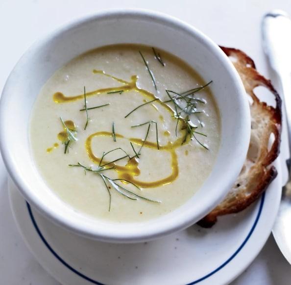 Fenyklová polévka v bílé misce, zdobená koprem a olivovým olejem.