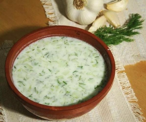 Studená polévka tarator z okurky v hnědé misce.