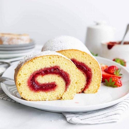 Piškot s jahodami, ve formě rolády, plněný jahodovým džemem, sypaný cukrem a podávaný s čerstvými jahodami.