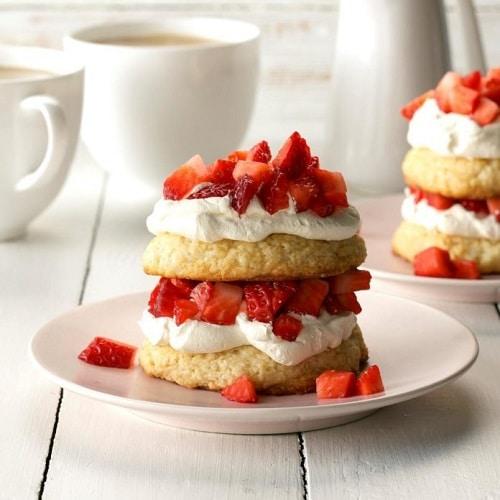 Dietní jahodový dezert, ve formě kulatých sušenek, zdobený šlehačkou a čerstvými nakrájenými jahodami.