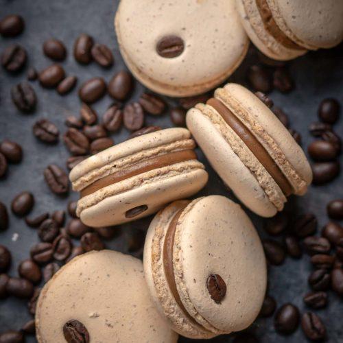 Plněné makronkové sušenky mezi zrnky kávy