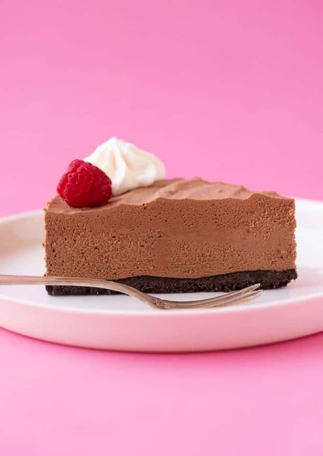 Jeden kousek nepečeného dortu z čokoládové pěny, ozdobeného šlehačkou a malinou