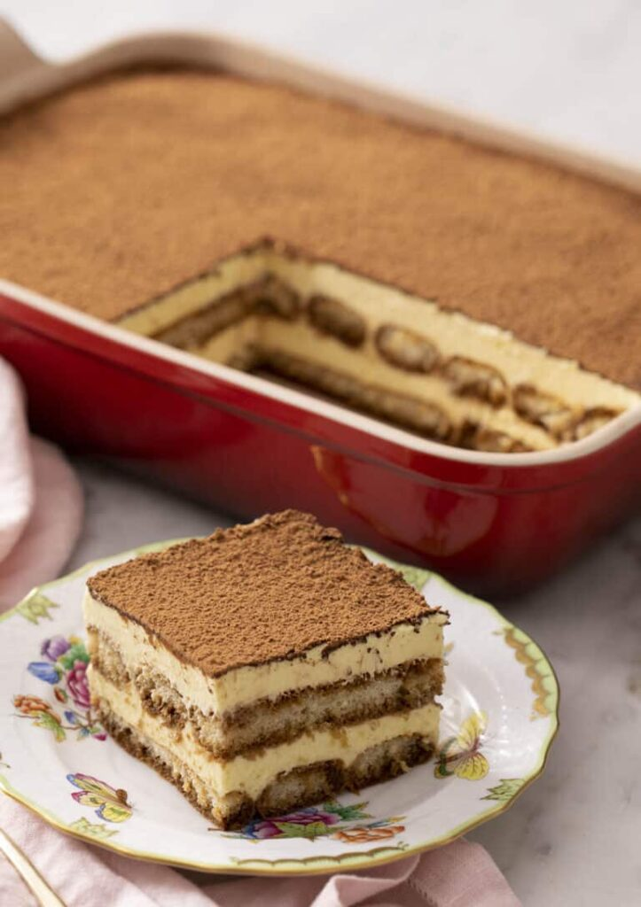Kostka tiramisu na talířku s pekáčkem rozkrojeného dortu v pozadí