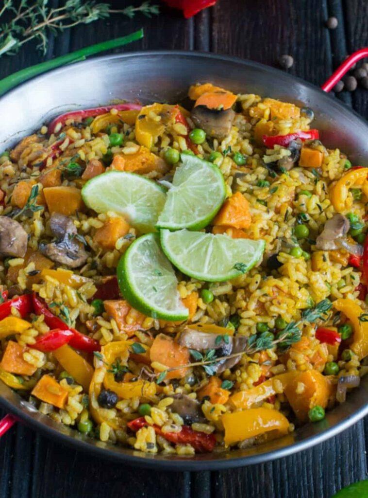 Směs rýže a zeleniny v pánvi ozdobená limetkovými plátky