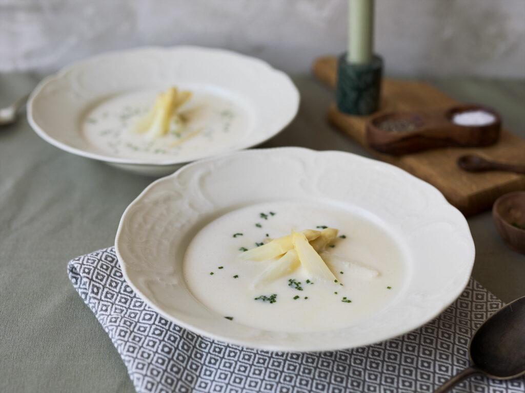 Dva talíře s bílou polévkou s několika kousky uvařených stonků chřestu uprostřed