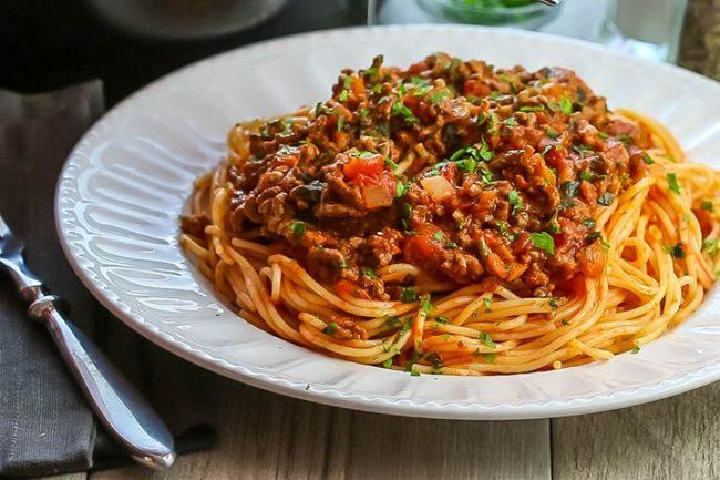 Špagety přelité boloňskou směsí z mletého masa a zeleniny na bílém talíři