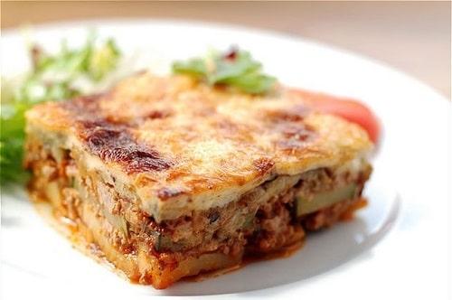 Bulharská musaka s mletým masem, servírovaná s čerstvým rajčetem a salátem na bílém talíři.