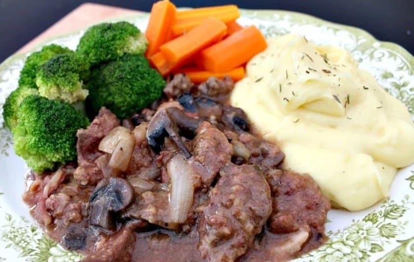 Dušená játrová směs s houbami, cibulí, bramborovou kaší a čerstvou zeleninou.