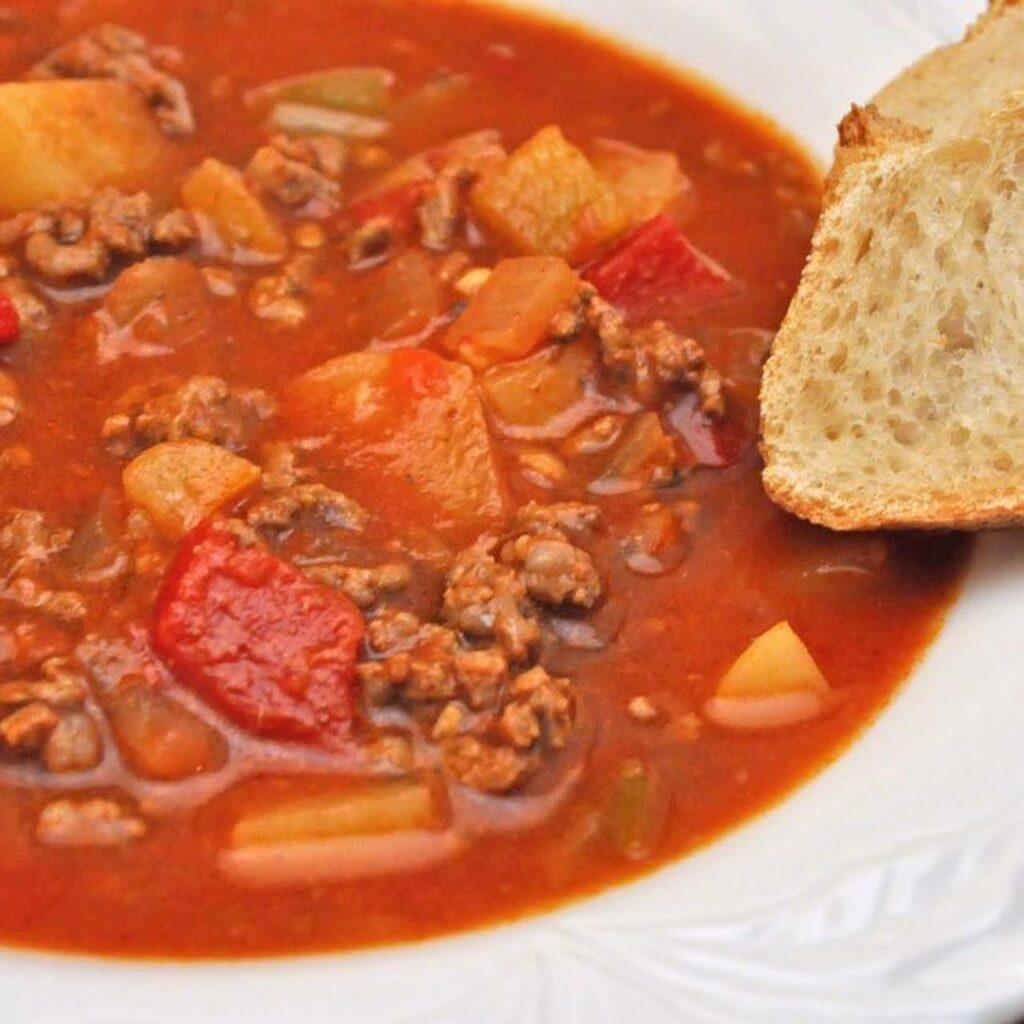Červená polévka s kousky brambor, pomletého masa a zeleniny s plátkem chleba na talíři