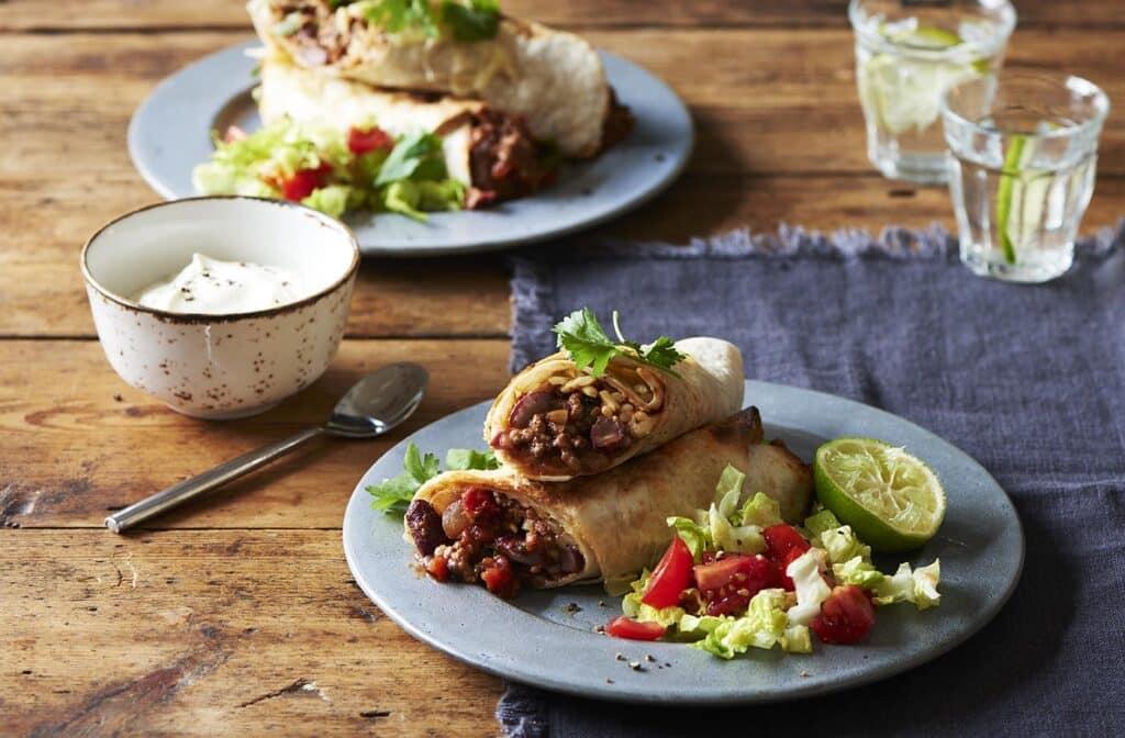 Dva talíře s rozkrojeným hovězím burritem a zeleninovou oblohou, miska se zakysanou smetanou