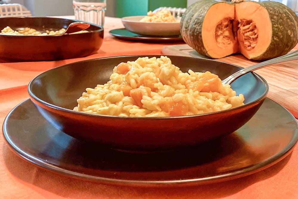 Pokrm z vařené rýže a dýně v hlubokém talíři na stole