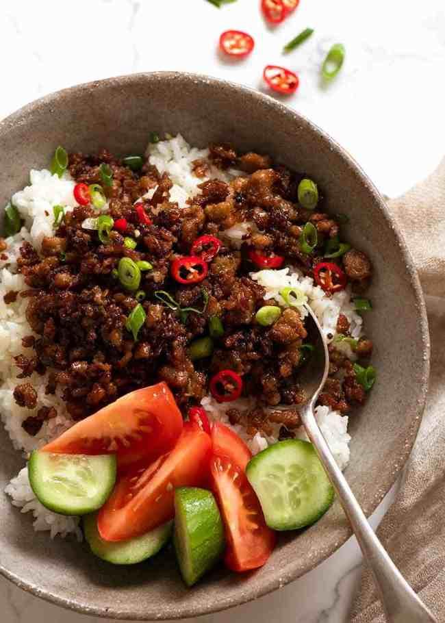 Jídelní miska naplněná rýží, opečeným vepřovým mletým masem a čerstvou zeleninou