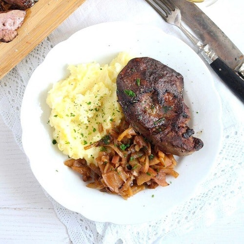 Játrový steak s bramborovou kaší, cibulí a jablky, zdobený petrželkou.