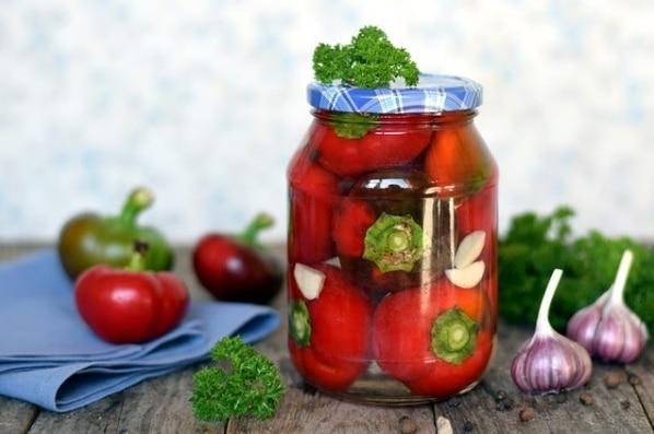 Nakládané papriky se zelím ve sklenici s modrým víkem.