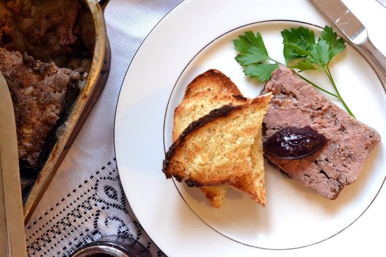 Plátek pečené pomazánky z kančího masa na talířku s chlebem a brusinkami