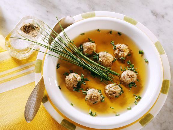 Polévka s játrovými knedlíčky, zdobená pažitkou.